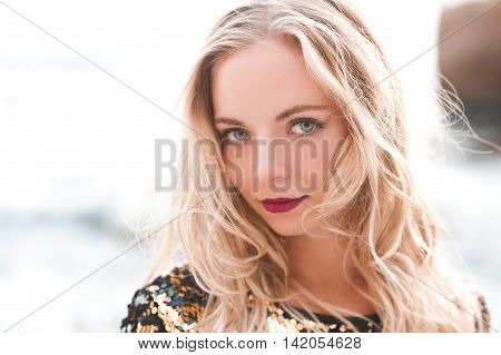 Smiling blonde girl 20-24 year old posing outdoors in sunny light. Looking at camera.