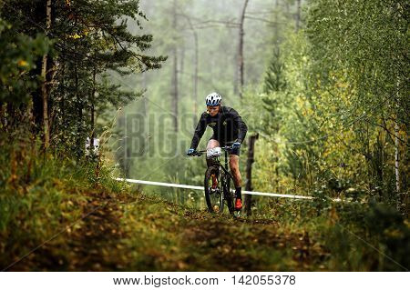 Revda Russia - July 31 2016: male athlete mountainbiker rides in forest during Regional competitions on cross-country bike