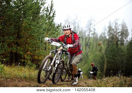 Revda Russia - July 31 2016: group athletes cyclists going uphill with your mountainbike during Regional competitions on cross-country bike