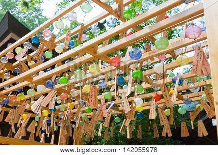 KAWAGOE JAPAN - 20 JULY 2016 - Glass wind chimes hang from wood structure at Hikawa Shrine in Kawagoe town Japan on July 20 2016.