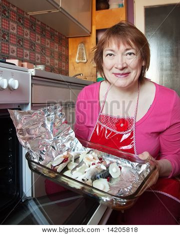 Woman putting mackerel with cranberry in griddle into oven poster