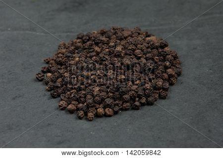 Black pepper corns on grey slate table