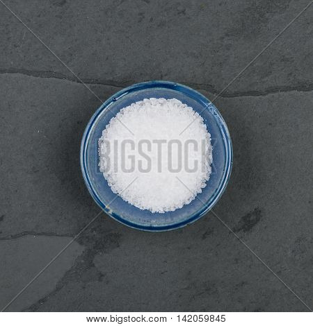 Small bowl of salt on a grey slate table