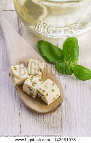 Traditional Greek feta cheese cubes on a wooden spoon