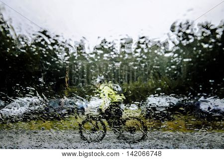 blurry image behind glass in rain cyclist riding on street
