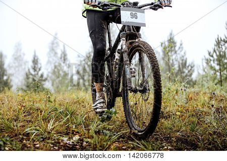 dirty feet of mountainbiker and bicycle wheel during competitions in cross-country