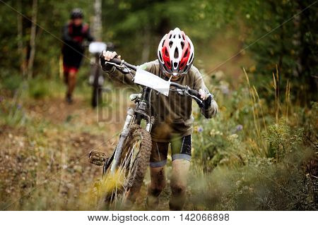 teen boy athlete mountainbike uphill on foot with his bicycle