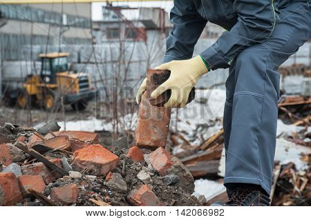 worker takes down blockages of broken bricks