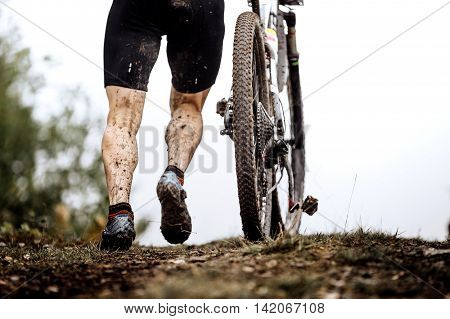 closeup dirty feet athlete mountainbiker and wheel of a sports bicycle
