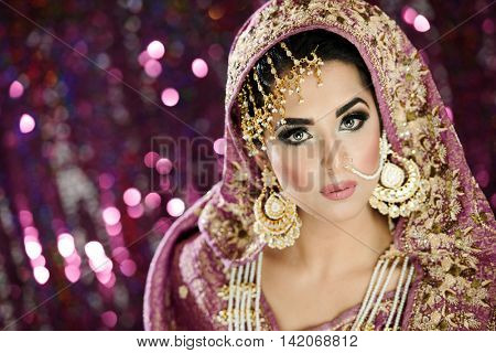Portrait of a beautiful female model in traditional Indian bride costume with heavy jewellery and makeup in landscape orientation poster