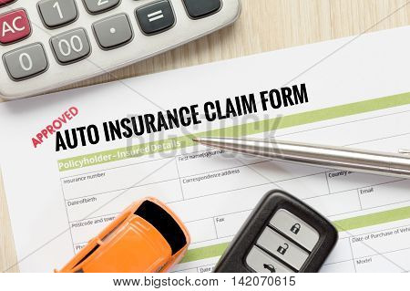 Top view of Approved auto insurance claim form with car key car toy and calculator on wooden desk - business concept