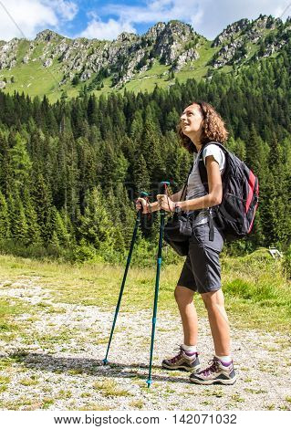 Young Woman doing hiking with trekking poles in a mountain path