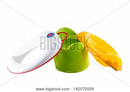 Green plastic potty and two removable toilet seats for children, one in the shape of a duck.