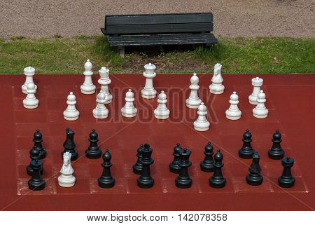 White and black chess pieces of large size for outdoor games.