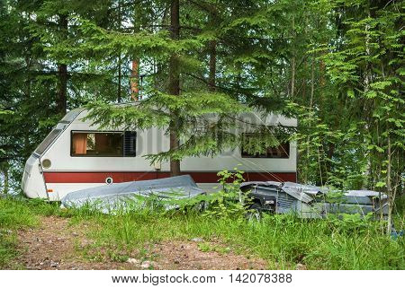House-trailer parked in the forest on the lake shore.