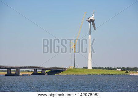 Construction site new Dutch windturbine near concrete bridge