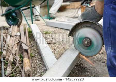 Construction worker cutting a reinforced concrete pillar for installation with coworker in the background resting. Construction business do-it-yourself dirty and dangerous work around the house concept.