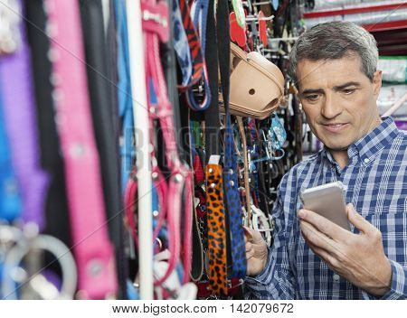 Customer Using Mobilephone While Buying Pet Leash