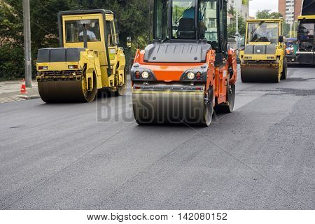 Compactor roller during road construction at asphalting work