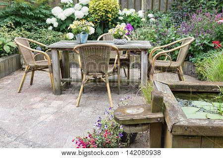 Wooden table and chairs in a ornamental garden with pond
