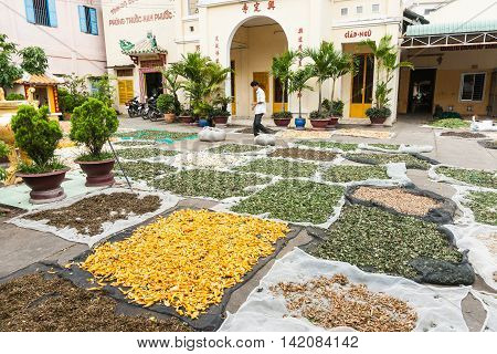 Can Tho, Vietnam - October 15, 2013: Patterns and colors in variety of formed by sheets of herbs out drying for later sale in courtyard of Vietnamese monastery