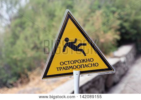 triangular yellow sign with inscription caution traumatic and image of falling man closeup