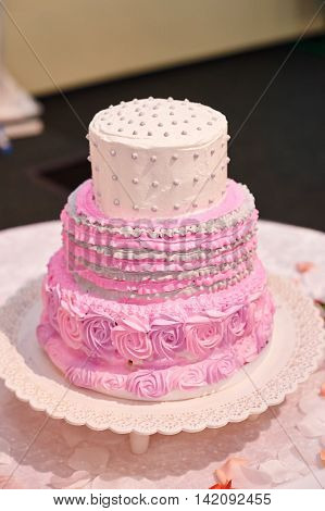 beautiful pink three-tiered wedding cake on table.