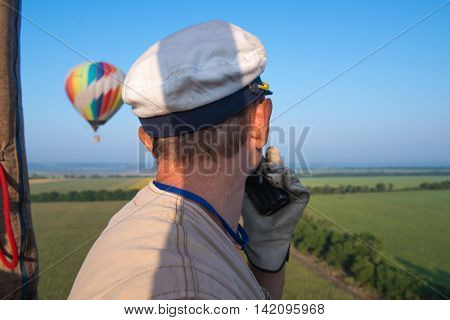 Aeronautics. The pilot balloon. View from the balloon's basket. Amazing view from the height of the balloon. Summer beautiful fields landscape from the bird's eye, sunrise. Ballooning.