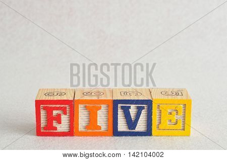 The word five (5) spelled with colorful alphabet blocks isolated against a white background
