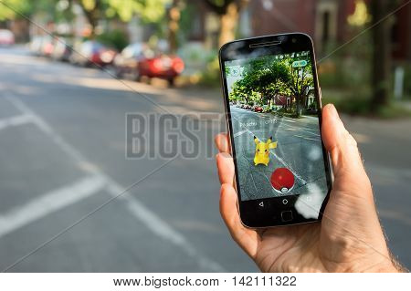 Montreal CA - August 10 2016: Closeup of a man playing Pokemon Go on a smart phone. Pokemon Go is a virtual reality game released in July 2016.