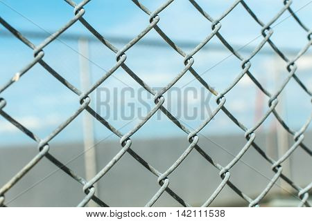 Chain link fence with barbed wire against evening sky