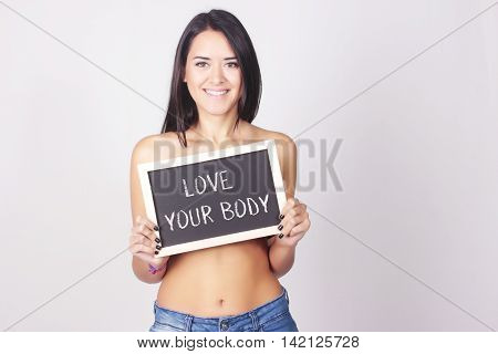 Young woman holding chalkboard that reads Love Your Body. Self love concept.