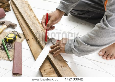 Male carpenter working with wood pencil  with machinist square at work place.Background craftsman tool.Zoom in