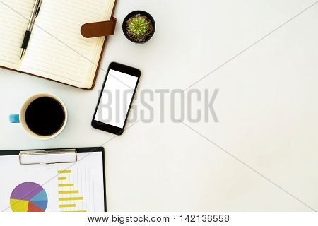 White office desk table with pen leather notebook chart or graph over backboard blank screen smartphone and cup of coffee. Top view with copy space