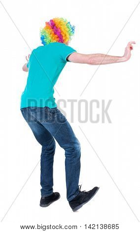 back view of dancing young beautiful  man  in clown wig.  Rear view people collection.  backside view of person.  Isolated over white background. Curly man in a turquoise sweater and clown wig dancing