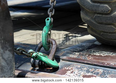 Iron hooks and chains attached to steel ring to secure load on flatbed truck.