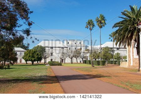NEW NORCIA,WA,AUSTRALIA-JULY 15,2016: The Benedictine Monastery with tropical palm trees under a blue sky in the historic monastic town of New Norcia, Western Australia.