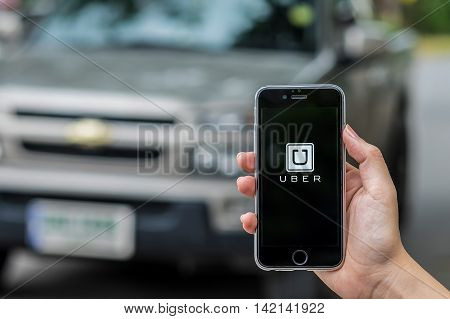 CHIANG MAITHAILAND - JUL 242016 : A MAN hand holding Uber app showing on iphone 6s. Uber is smartphone app-based transportation network