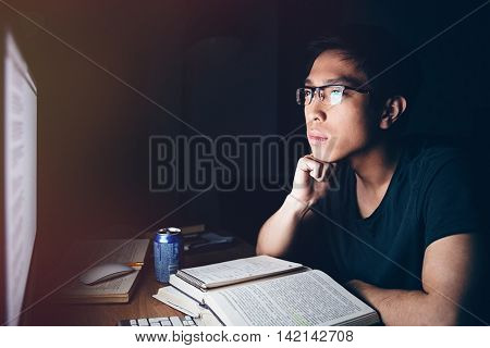 Serious asian young man sitting and studying with books and computer in dark room