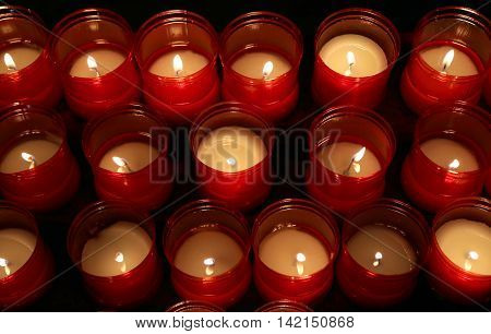 Red Flames Of Candles Lit By The Faithful In The Place Of Worshi