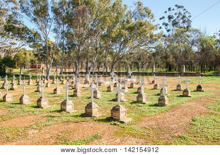 NEW NORCIA,WA,AUSTRALIA-JULY 15,2016: Old cemetery with headstones and crosses in organised pattern with trees and a blue sky in the monastic town of New Norcia, Western Australia.
