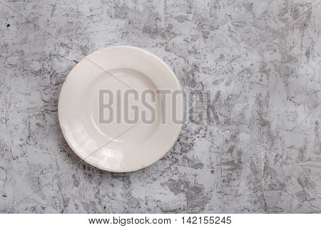 White empty vintage plate on light gray rough background with copy space top view