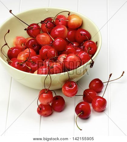 Heap of Fresh Ripe Sweet Maraschino Cherries in Green Bowl closeup on Plank White background