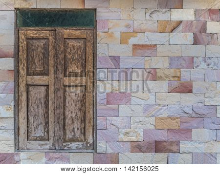 Old style wooden window and pattern glass on colorful modern style square pattern limestone brick wall with copy space