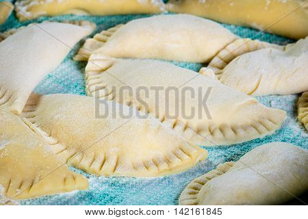 Homemade Agnolotti filled with ricotta on green cloth