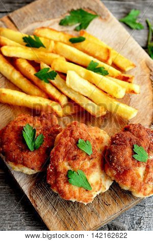Turkey breast cutlets served with deep fried potatoes on cutting board and on an old wooden background. Cutlets prepared from minced meat and fried in vegetable oil in a frying pan. Closeup. Top view