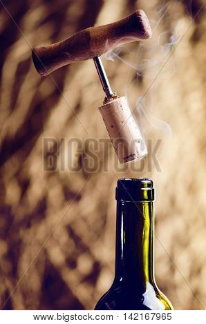 Opening a wine bottle with a corkscrew on a golden background. Wine bottle with steam. Levitation of corkscrew. Isolated.