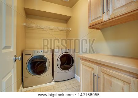 Beige Laundry With Modern Appliances And Tile Floor.