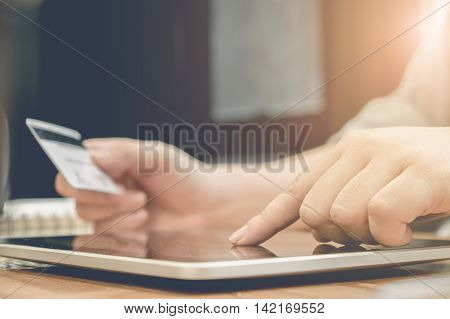 Online paymentWoman's hands holding a credit card and using tablet for online shopping with vintage filter effect