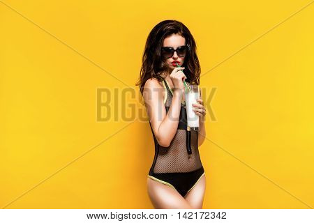 Portrait of sexy brunette in black beachwear and sunglasses drinking cocktail.Isolated. Retouched photo.